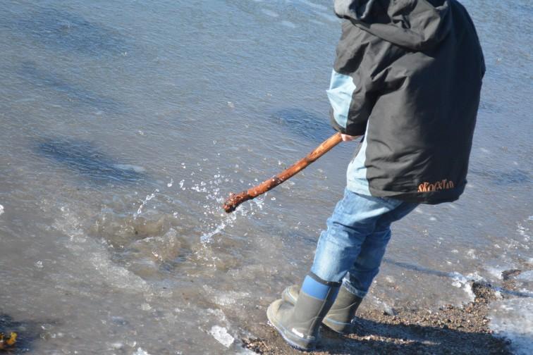 slår i stykker isen og vannet spruter