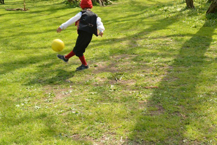Gutt spiller fotball i bunad