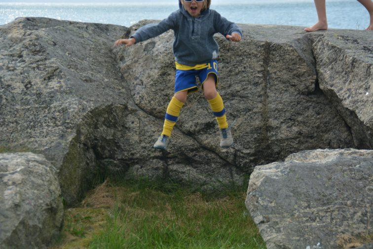 Gutt hopper ned fra en liten fjellskrent